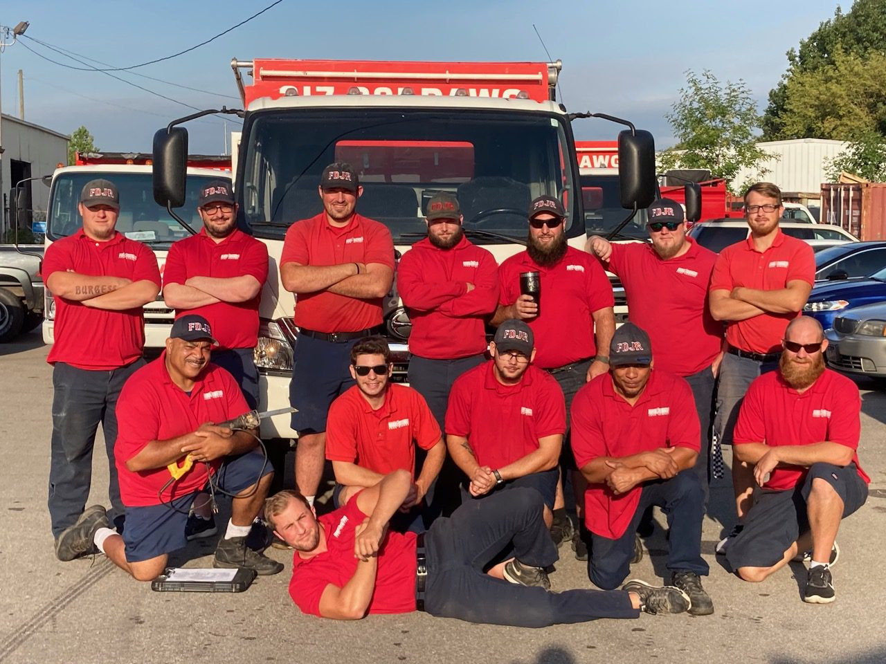 Image of Fire Dawgs Junk Removal team posing in front of their truck